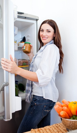 Positive woman taking something of the fridge photo