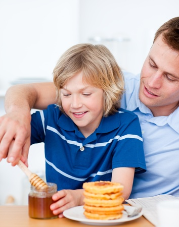 Adorable boy and his father putting honey on waffles photo