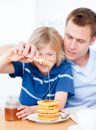 Smiling boy and his father putting honey on waffles photo