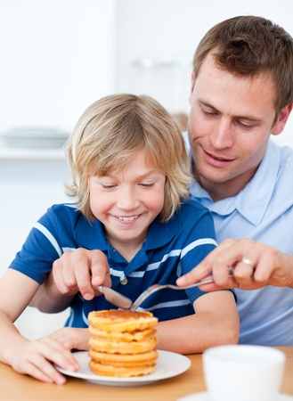 Attentive father and his son eating waffles photo