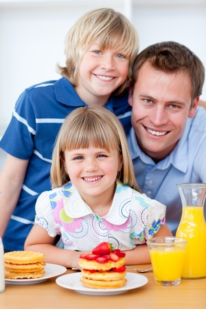 Happy family eating waffles with strawberries photo