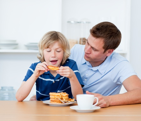 Charming father and his son eating waffles photo