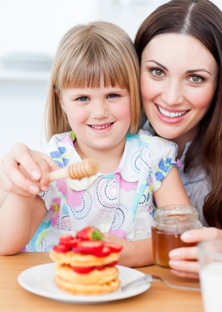 Adorable little girl and her mother putting honey on waffles photo