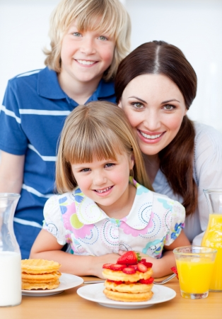Jolly mother and her children eating waffles with strawberries photo