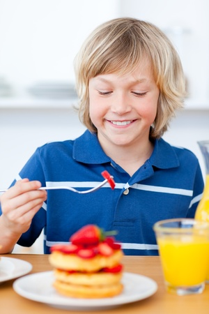 Adorable boy eating waffles with strawberries photo