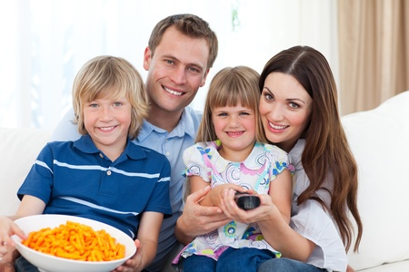 house series: Happy family watching television and eating chips