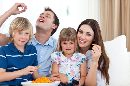 Young family eating crisps while watching TV  photo