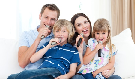 child singing: Happy family singing a karaoke together