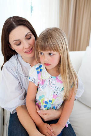 Cute blond girl sitting on her mothers lap photo