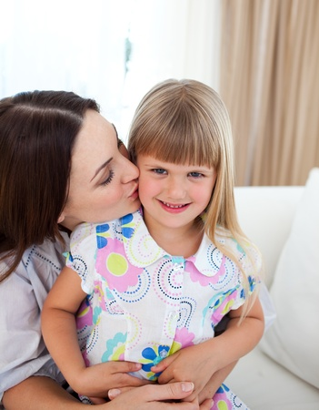 Attentive mother kissing her little girl Stock Photo - 10258346