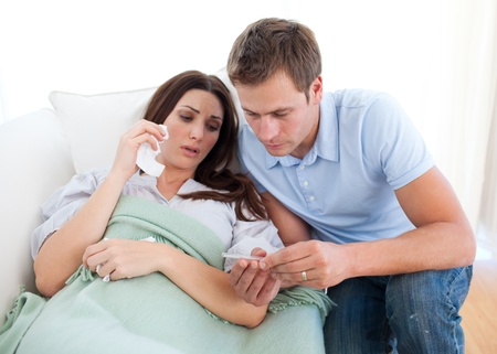 Husband taking his wife's temperature lying on the sofa Stock Photo - 10259098