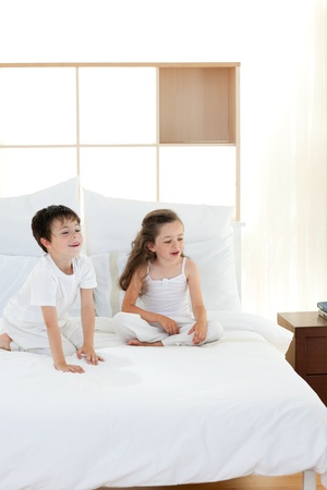 Brother and sister having fun in parents bedroom photo