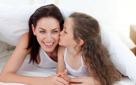 mother with child: Mother and her daughter having fun on bed Stock Photo