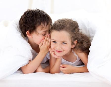brat: Mały chłopiec mówi w tajemnicy do siostry