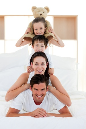 Young Family playing on bed together photo