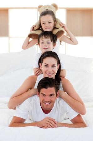 familia abrazo: Padres y ni�os jugando juntos en la cama  Foto de archivo