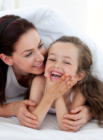 Little girl and her mother having fun on bed photo