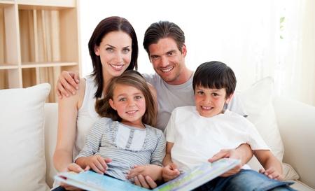 familia abrazo: Familia leyendo un libro en el sof�