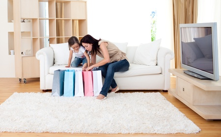 Jolly mother and her daughter at home after shopping photo