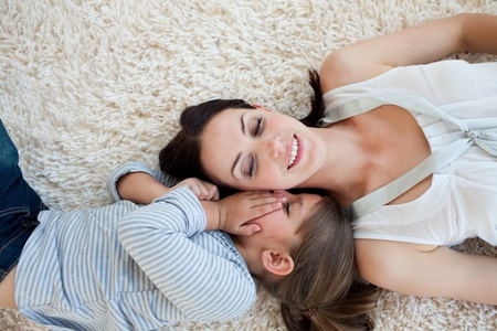 Smiling mother and her daughter lying on the floor photo