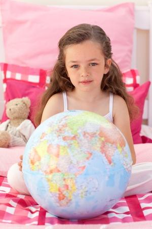Little girl holding a terrestrial globe photo