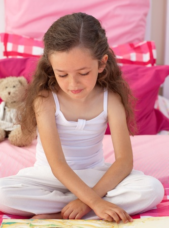 Cute girl reading on bed photo