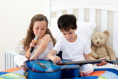 little boy and girl: Siblings singing and playing guitar Stock Photo