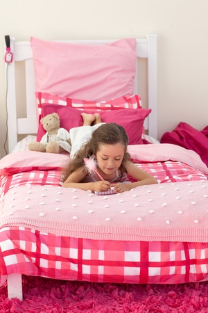 Little girl writing on bed photo