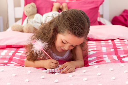 Close-up of a Little girl writing on bed photo