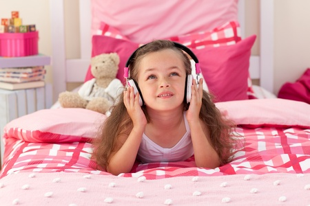 Cute girl listening music in the bedroom photo