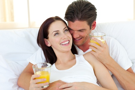 Young couple drinking orange juice lying on their bed