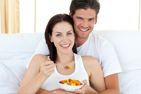 Happy couple eating fruits lying on their bed photo