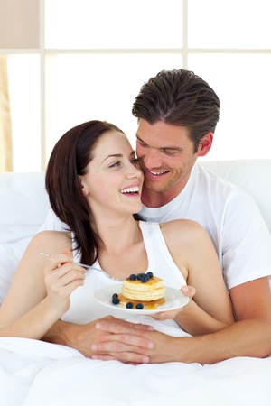 Joyful couple eating pancakes lying on their bed photo