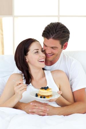 pareja comiendo: Pareja alegre comer panqueques acostado en su cama