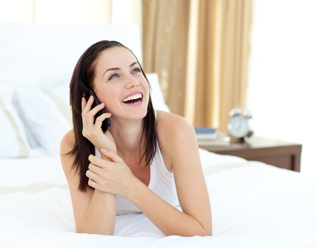 Radiant woman on phone lying on her bed  photo