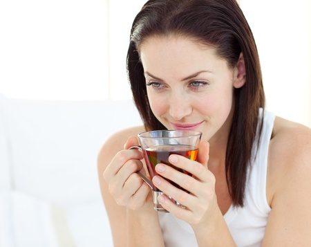 Delighted woman drinking a tea  photo