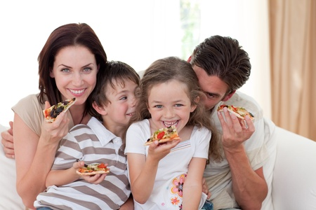Lachende familie eten pizza