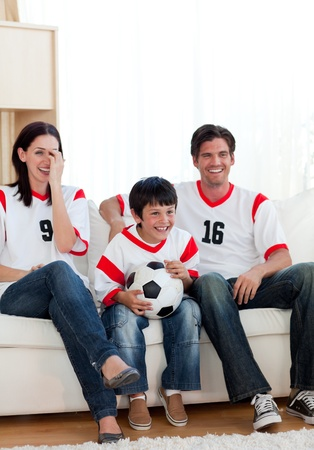 Positive family watching football match photo