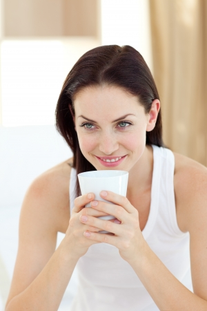 Radiant woman drinking a coffee photo