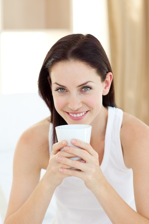 women holding cup: Bright woman drinking a coffee