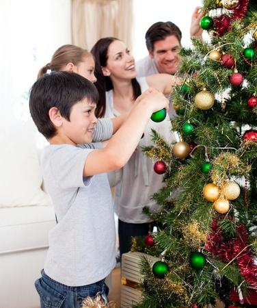 Familia feliz decorando un árbol de navidad con boubles Foto de archivo