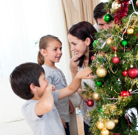 Smiling family decorating a Christmas tree with boubles Stock Photo