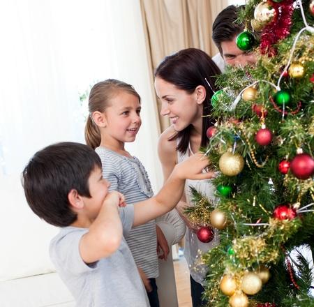 pere noel: Souriant famille d�corant un arbre de No�l avec boubles
