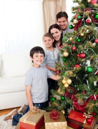 angel tree: Happy family decorating a Christmas tree with boubles and presents