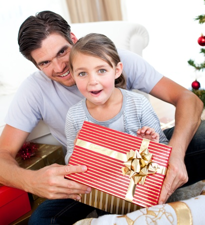 Surprised little girl opening a Christmas present with her father Stock Photo - 10257000