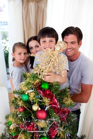 Happy family decorating a Christmas tree photo