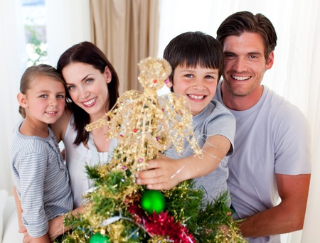 Portrait of a family decorating a Christmas tree photo