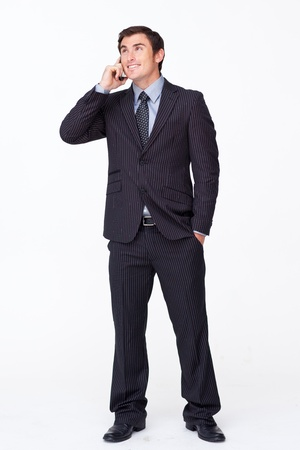 Attractive businessman on mobile phone against white photo