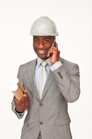 Attractive ethnic architect on phone holding plans photo