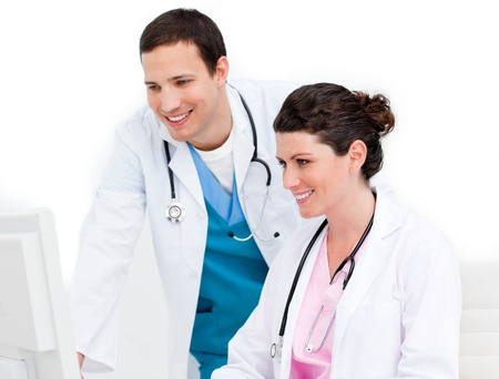 Smiling medical team working at a computer photo